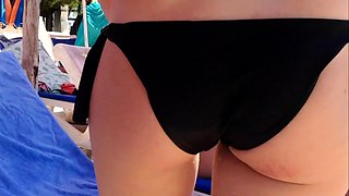 Ravishing blonde in a sexy black bikini enjoys the hot sun