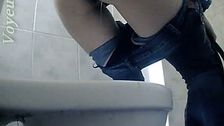 Sexy lean white chick in tight jeans pissing in the toilet