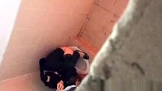Asian woman spied over the toilet wall taking a pee