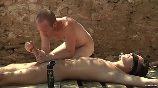 Dirty dude strokes and blows a massive pecker of his male slave